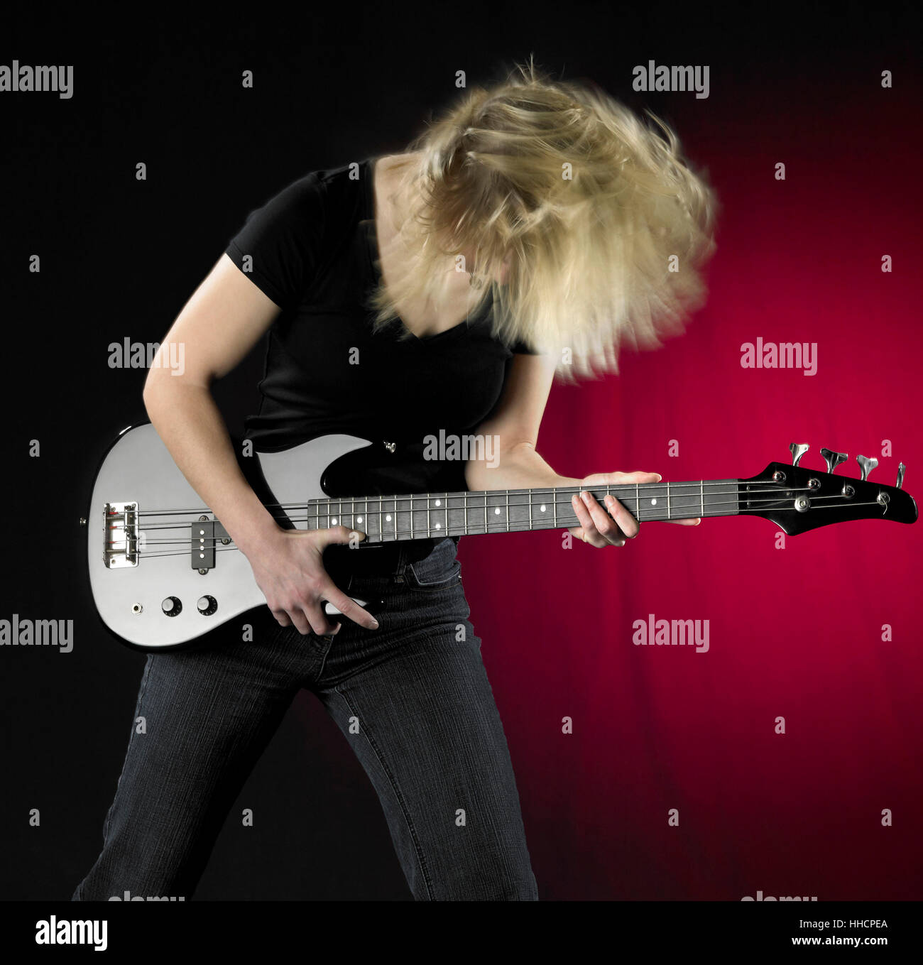 a woman playing a black bass guitar in front of partly reddish back Stock Photo