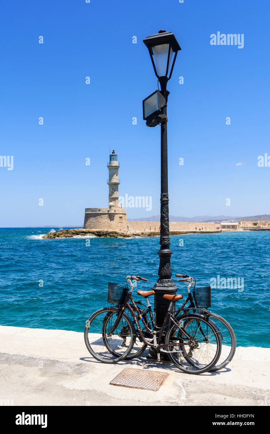 Bikes on the waterfront promenade in front of the old lighthouse in the Venetian harbour of Chania, Crete, Greece - Stock Image