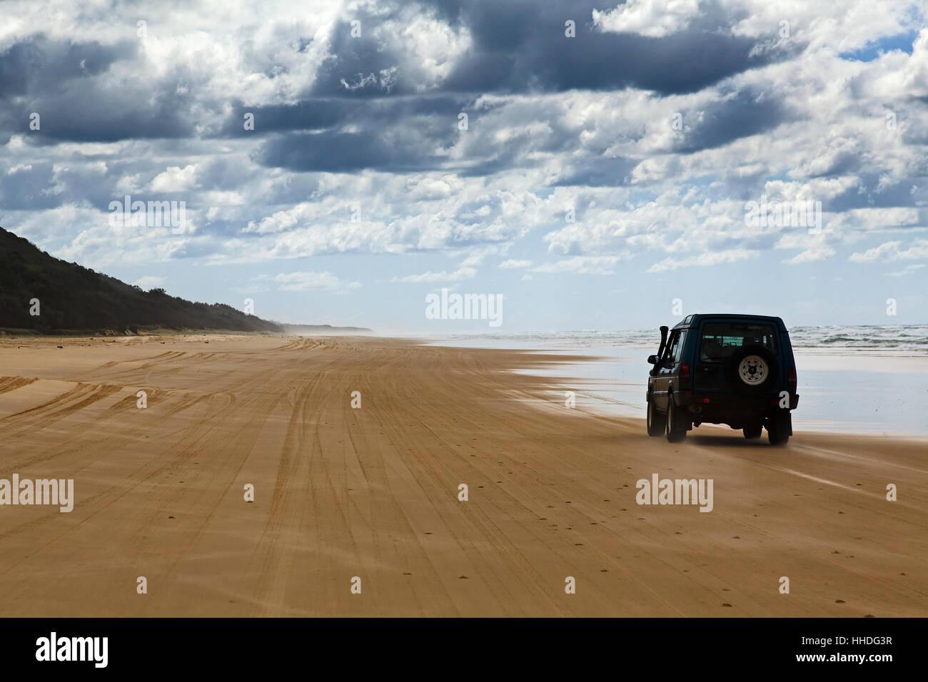 Main transportation highway on Fraser Island - wide wet sand beach coast facing Pacific ocean - long 75 miles beach. - Stock Image