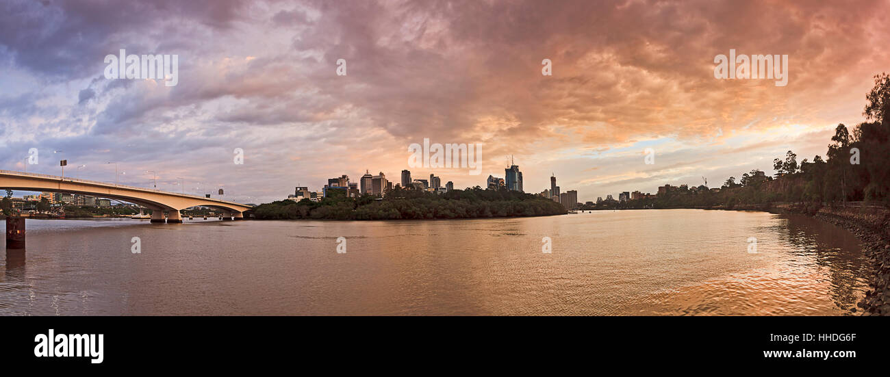 Brisbane city CBD panorama from Captain cook bridge to Story bridge along river bends at sunrise against urban skyscrapers - Stock Image