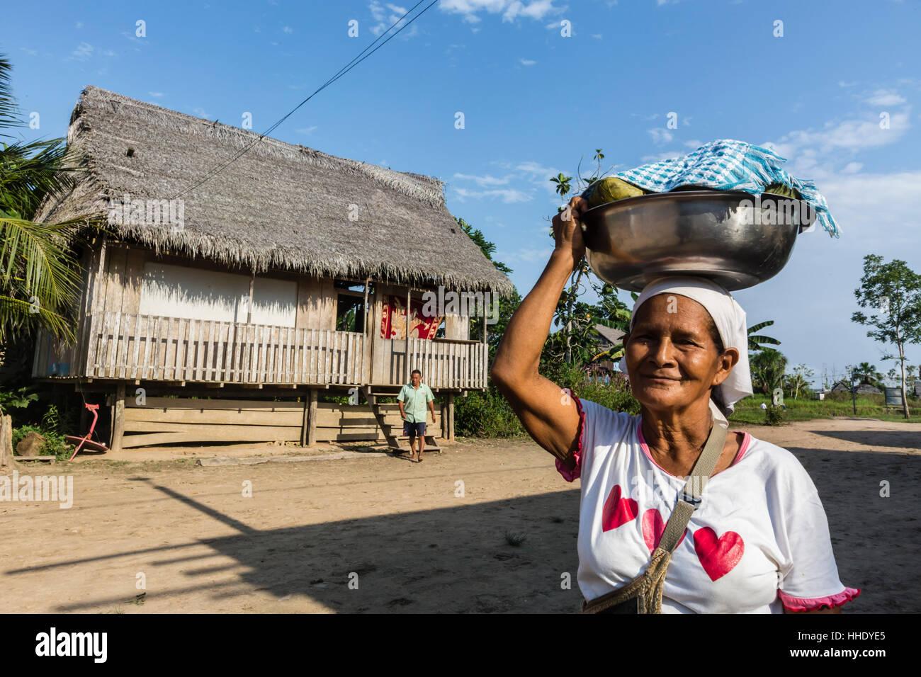 Woman carrying food in bowl, San Miguel Caño, Upper Amazon River Basin, Loreto, Peru - Stock Image