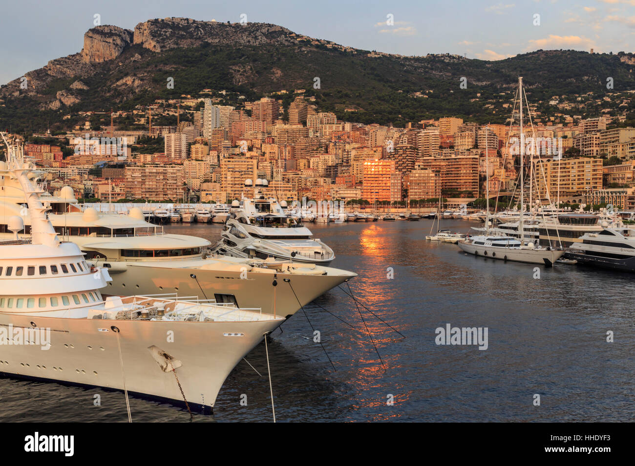 Huge super yachts in the glamorous Port of Monaco (Port Hercules) at sunrise, from the sea, Monte Carlo, Monaco, - Stock Image