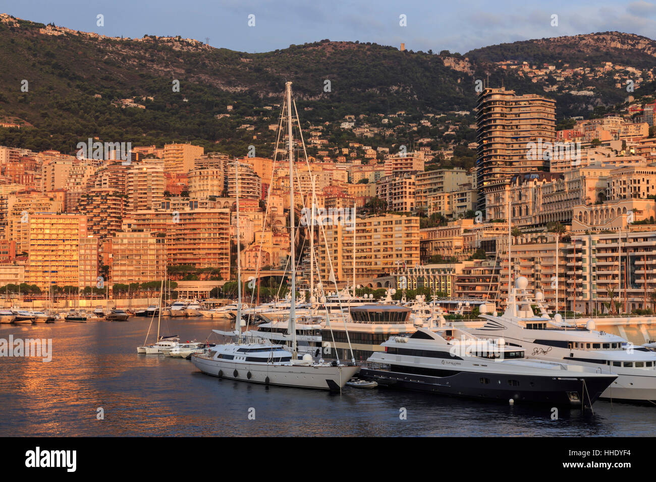 Yachts in the glamorous Port of Monaco (Port Hercules) at sunrise, from the sea, Monte Carlo, Monaco, Mediterranean - Stock Image