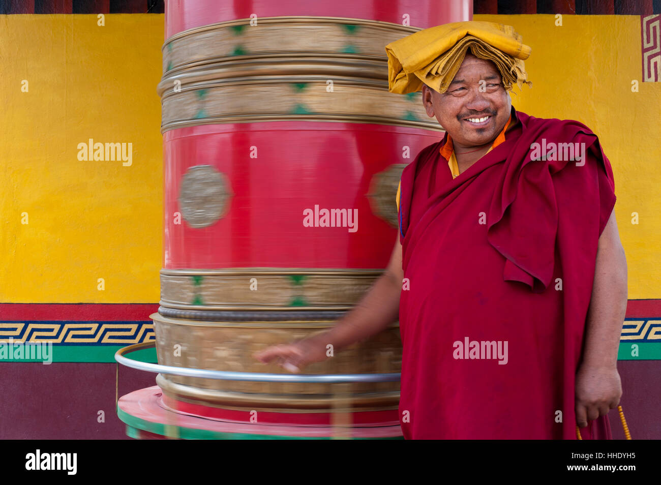 A Buddhist monk (lama) spins a prayer wheel at Diskit Monastery in the Nubra Valley, Ladakh, India - Stock Image