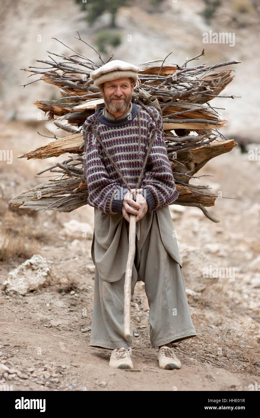 A Kalasha man carrying firewood, Kalasha valley, Chitral, North West Frontier Province, Pakistan - Stock Image
