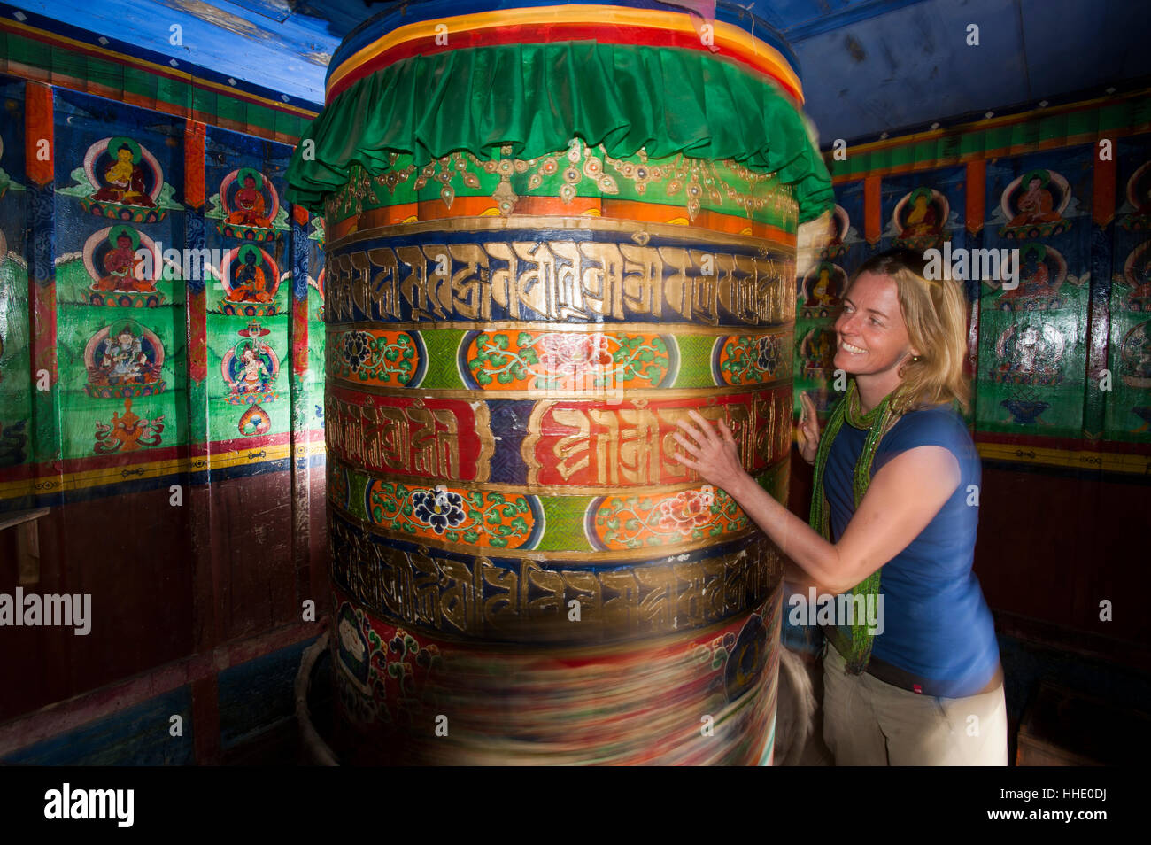 A trekker spins a Buddhist prayer wheel while trekking towards to Everest Base Camp, Khumbu Region, Nepal - Stock Image