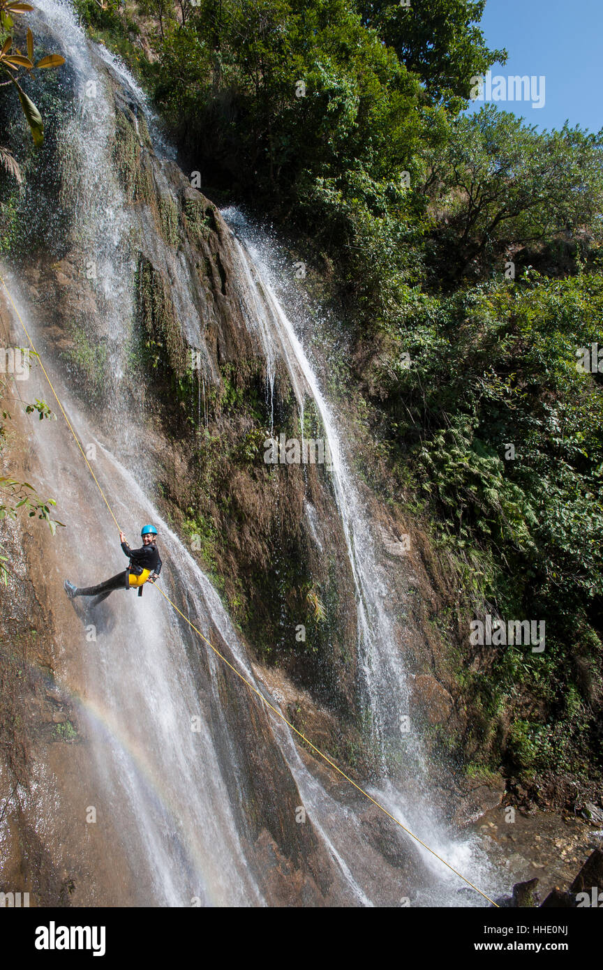 A girl pauses to smile for the camera while canyoning in a waterfall, Nepal - Stock Image