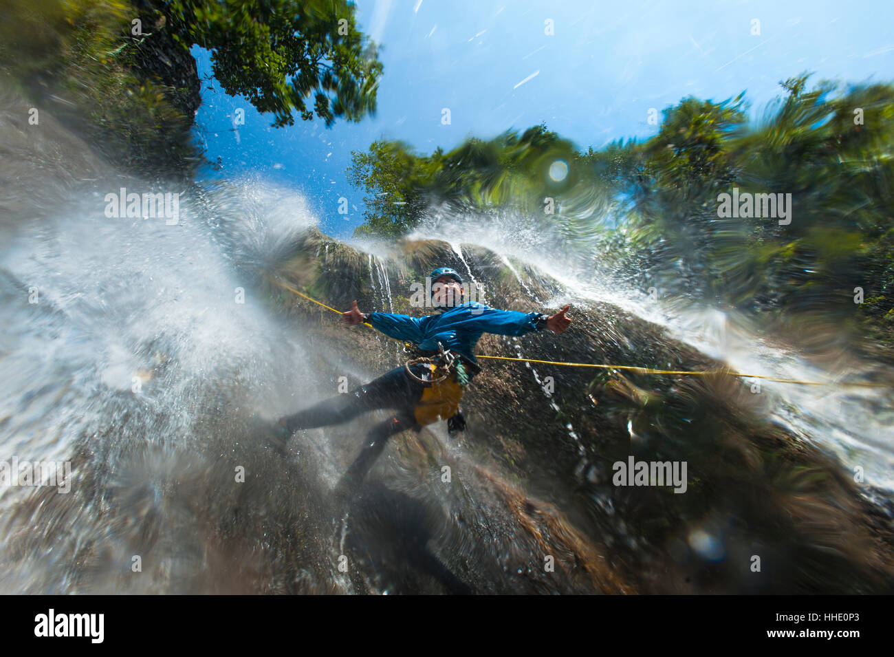 A man pauses to smile for the camera while canyoning in a waterfall, Nepal - Stock Image