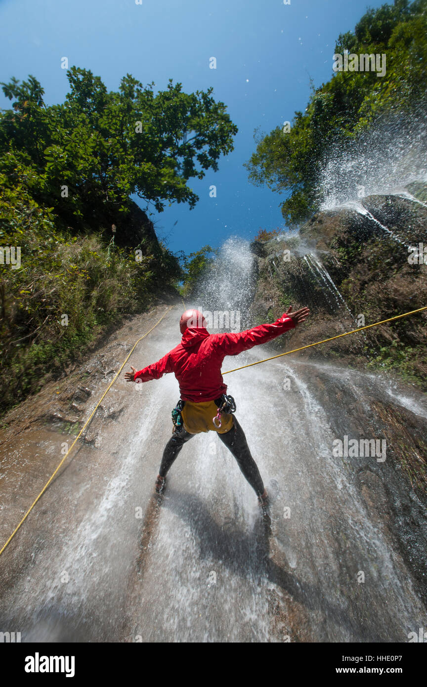 A man pauses to hold his arms in the falling water while canyoning, Nepal - Stock Image