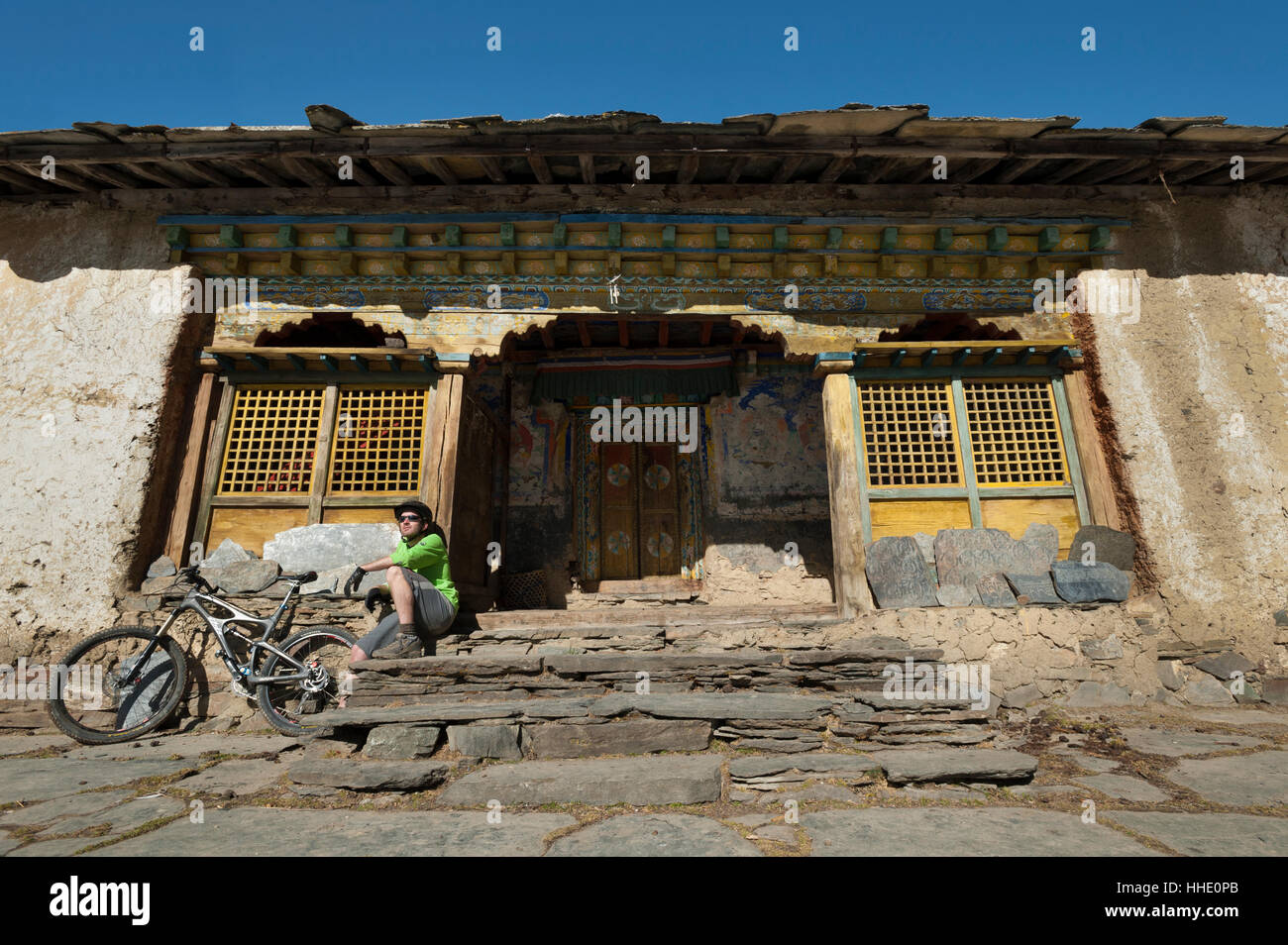 A mountain biker takes a well earned rest at Mu Gompa, the last village in the Tsum Valley, Nepal - Stock Image