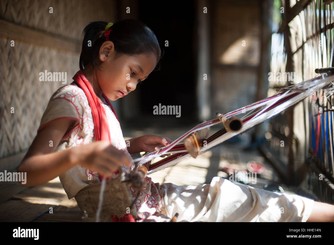 A little girl learns the skill of weaving on a handloom, Chittagong Hill Tracts, Bangladesh - Stock Image