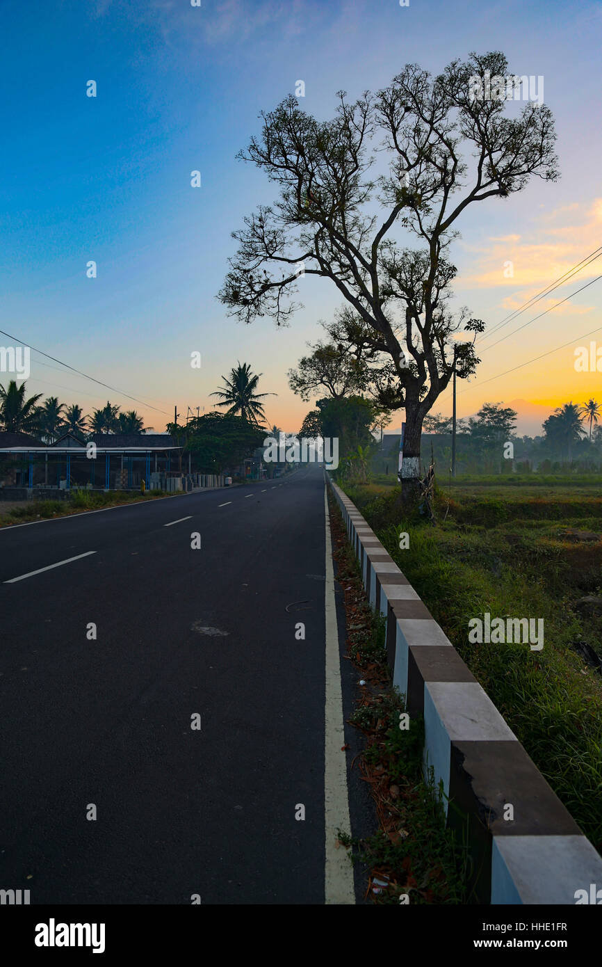 Quiet Road In Yogyakarta, Central Java, Indonesia. Rare lack of traffic during the early morning sun rise. Close - Stock Image
