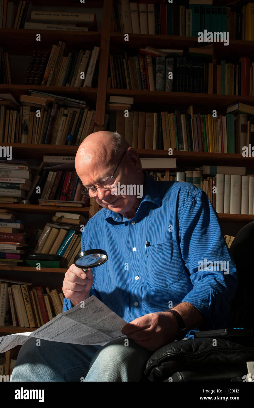 An older man reading with the aid of a magnifying glass at his home. - Stock Image