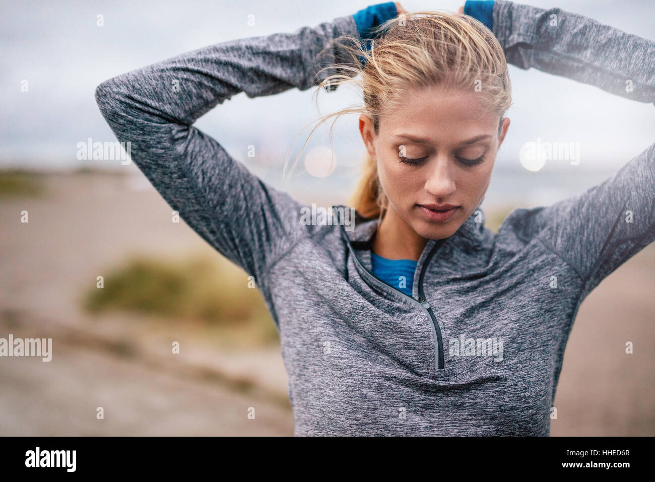 Fit female athlete tying hair before her workout outdoors. Young woman getting ready for training. - Stock Image