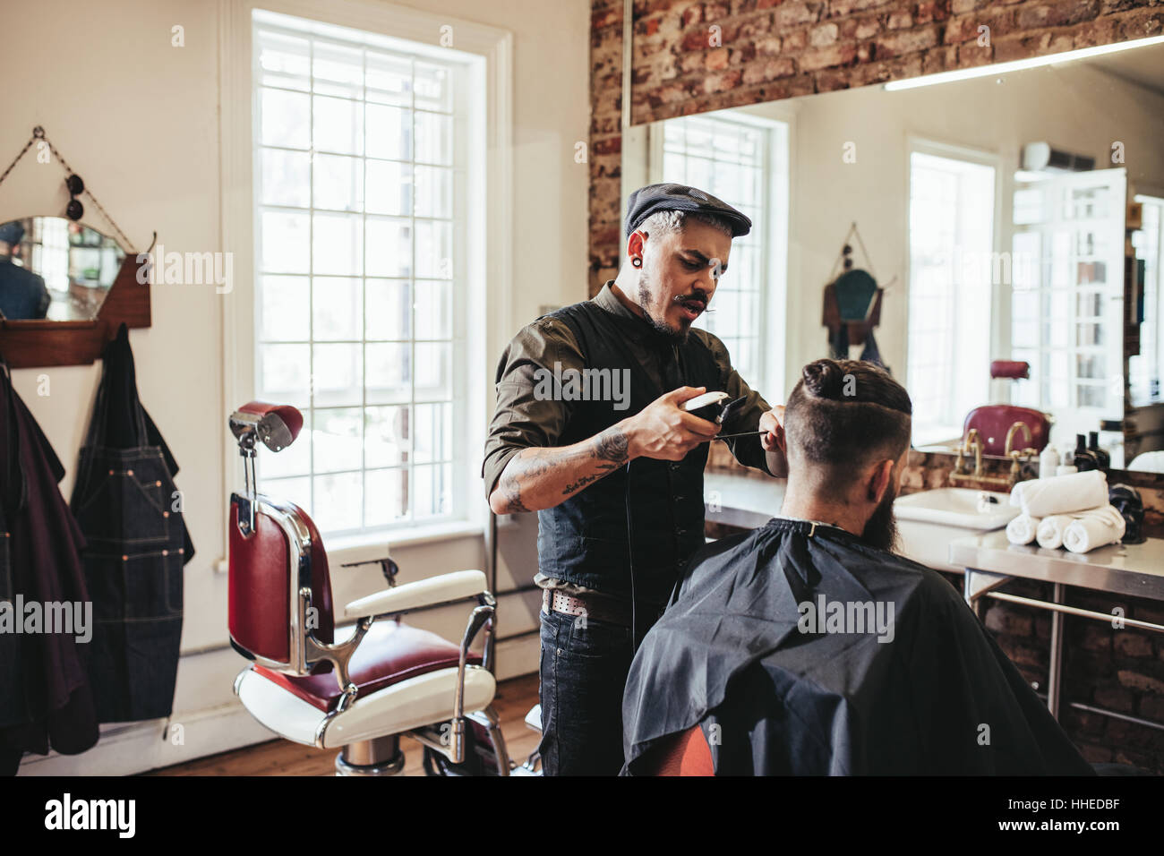Hairstylist serving client in salon. Young man getting trendy haircut at barbershop. - Stock Image