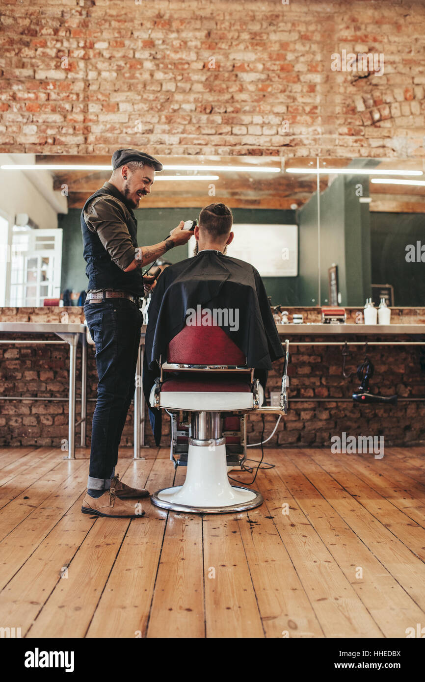 Hairdresser giving a haircut to male client at salon. Man getting haircut at barber shop. - Stock Image
