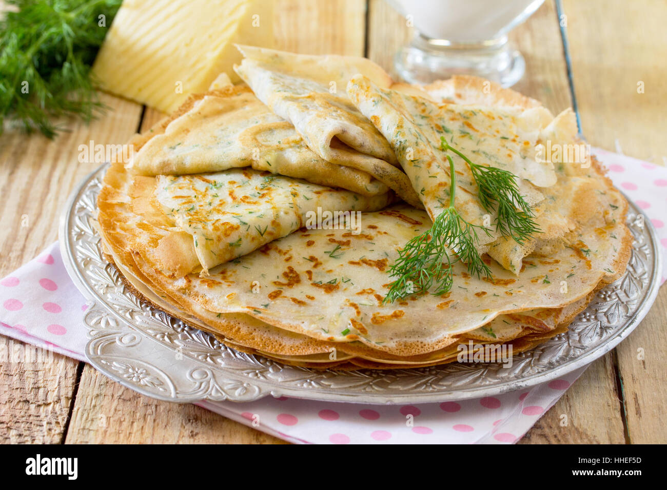 Not sweet pancakes with cheese and fresh dill on a wooden table. Breakfast, snack or brunch. Healthy food concept. - Stock Image
