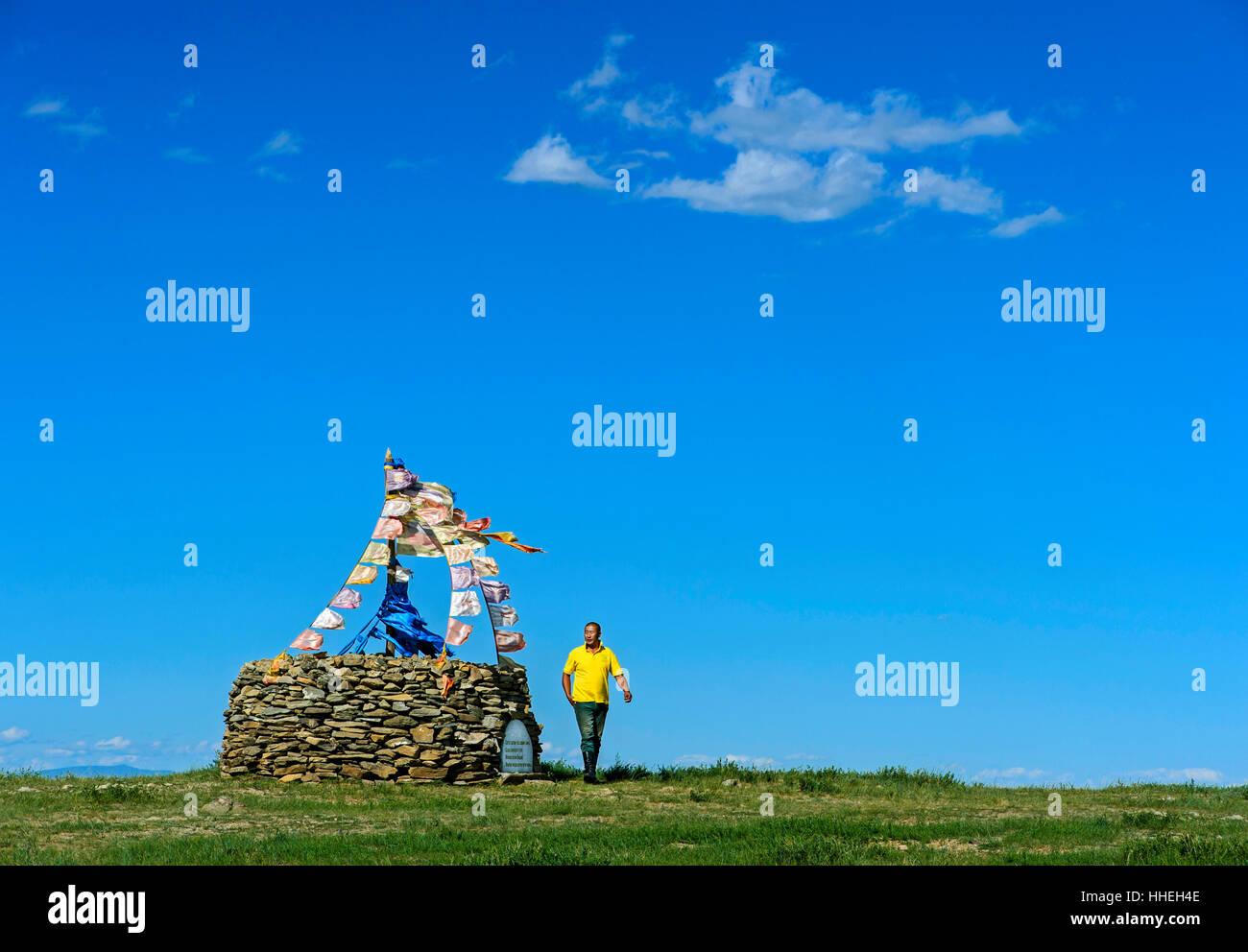 Mongolian man performing prayer ritual beside ovoo, sacred stone heap, Arkhangai, Mongolia - Stock Image
