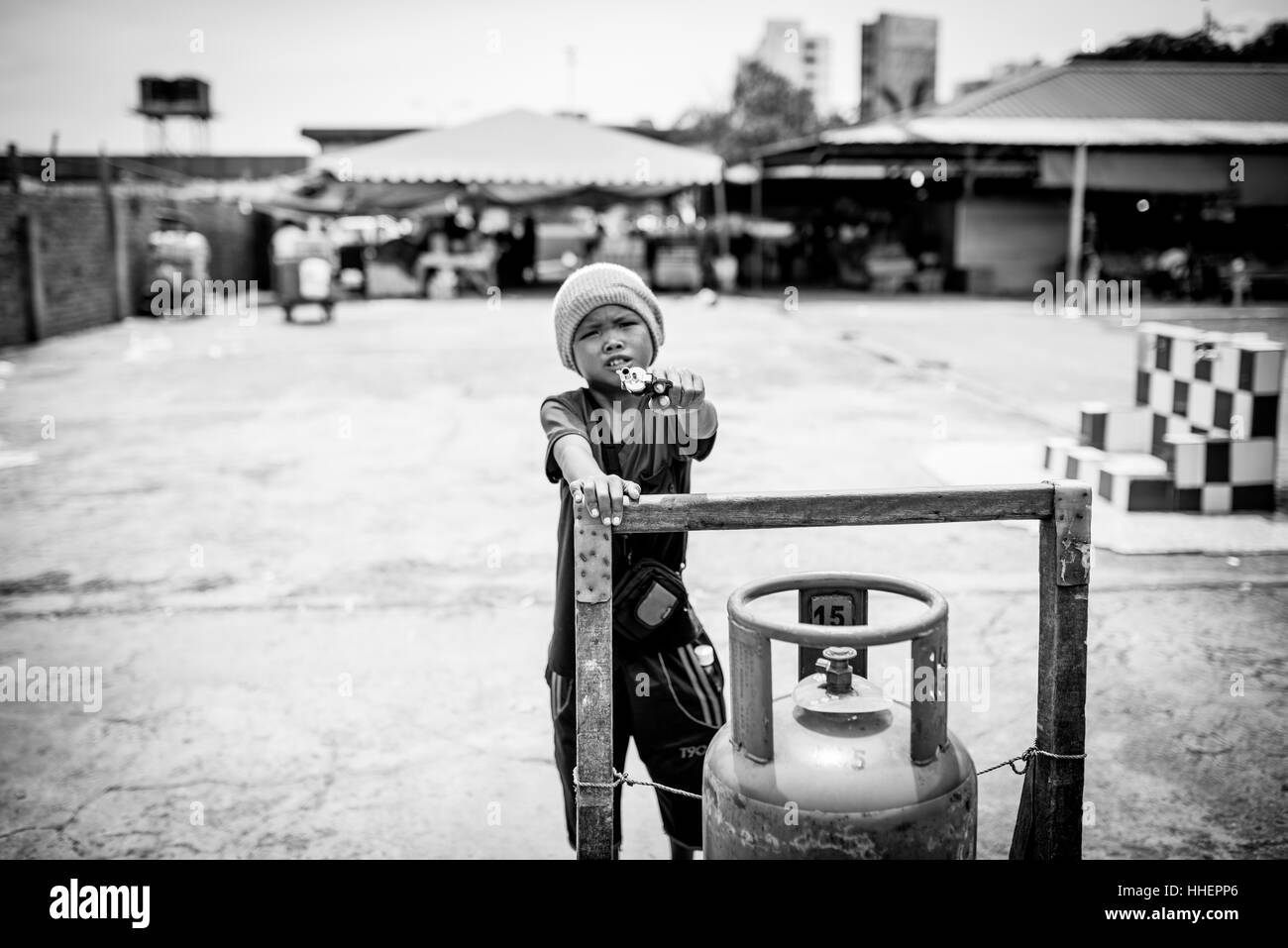 A young boy points a gun (assumed to be a toy) at me in Kota Kinabalu, Malaysia. - Stock Image