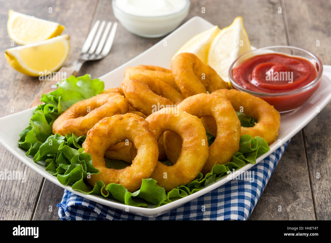 Fried calamari rings with lettuce and ketchup on wooden background - Stock Image