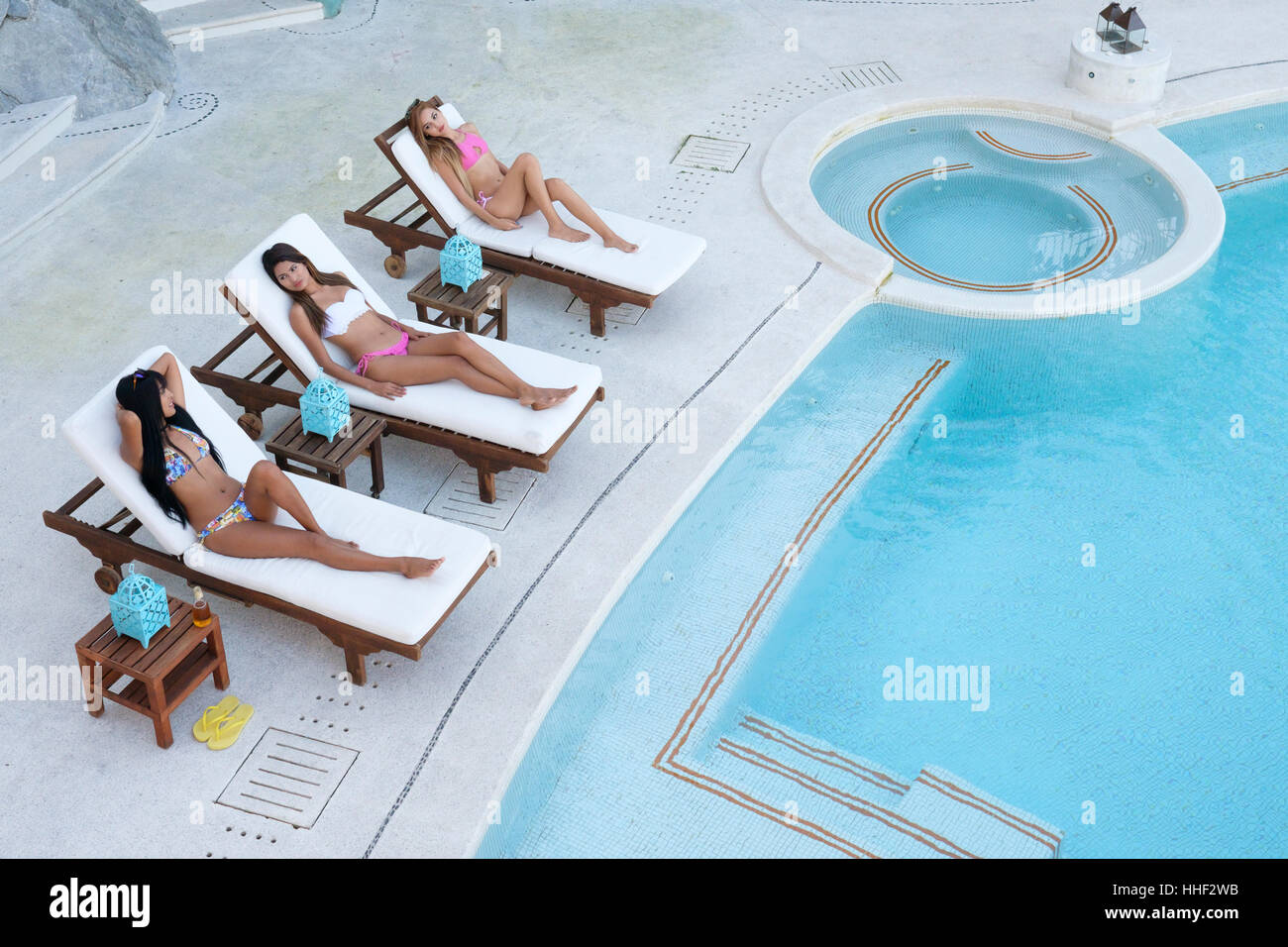 Three young attractive hispanic women using loungers for tanning next to swimming pool - Stock Image
