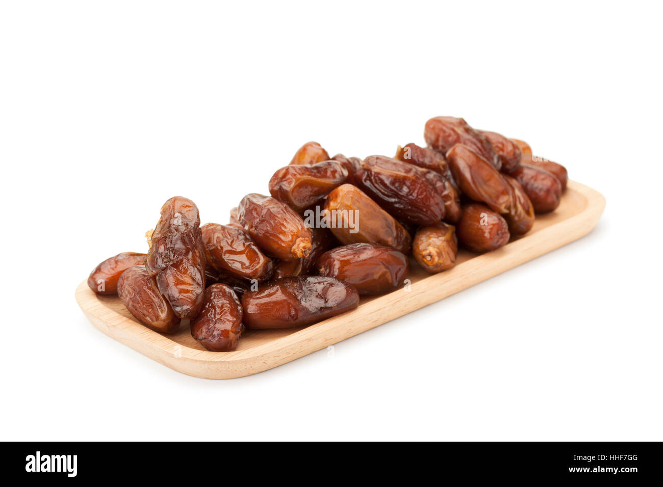 date palm dried fruit in wooden plate isolated on white background with clipping path - Stock Image