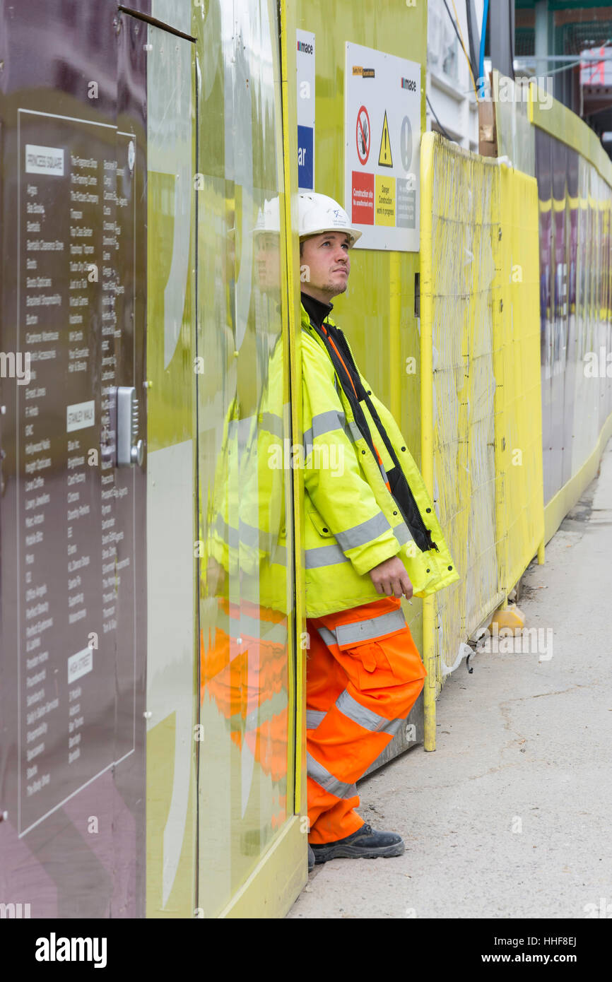 Young construction worker relaxing with cigarette, Bracknell, Berkshire, England, United Kingdom - Stock Image