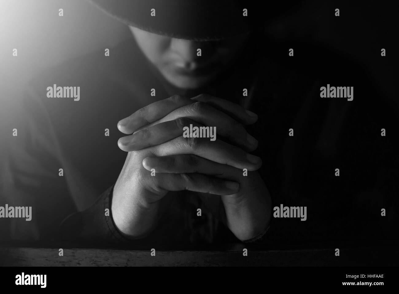Pray in the Darkness with shining light, Selective focus on hands, Dramatic and emotional - Stock Image