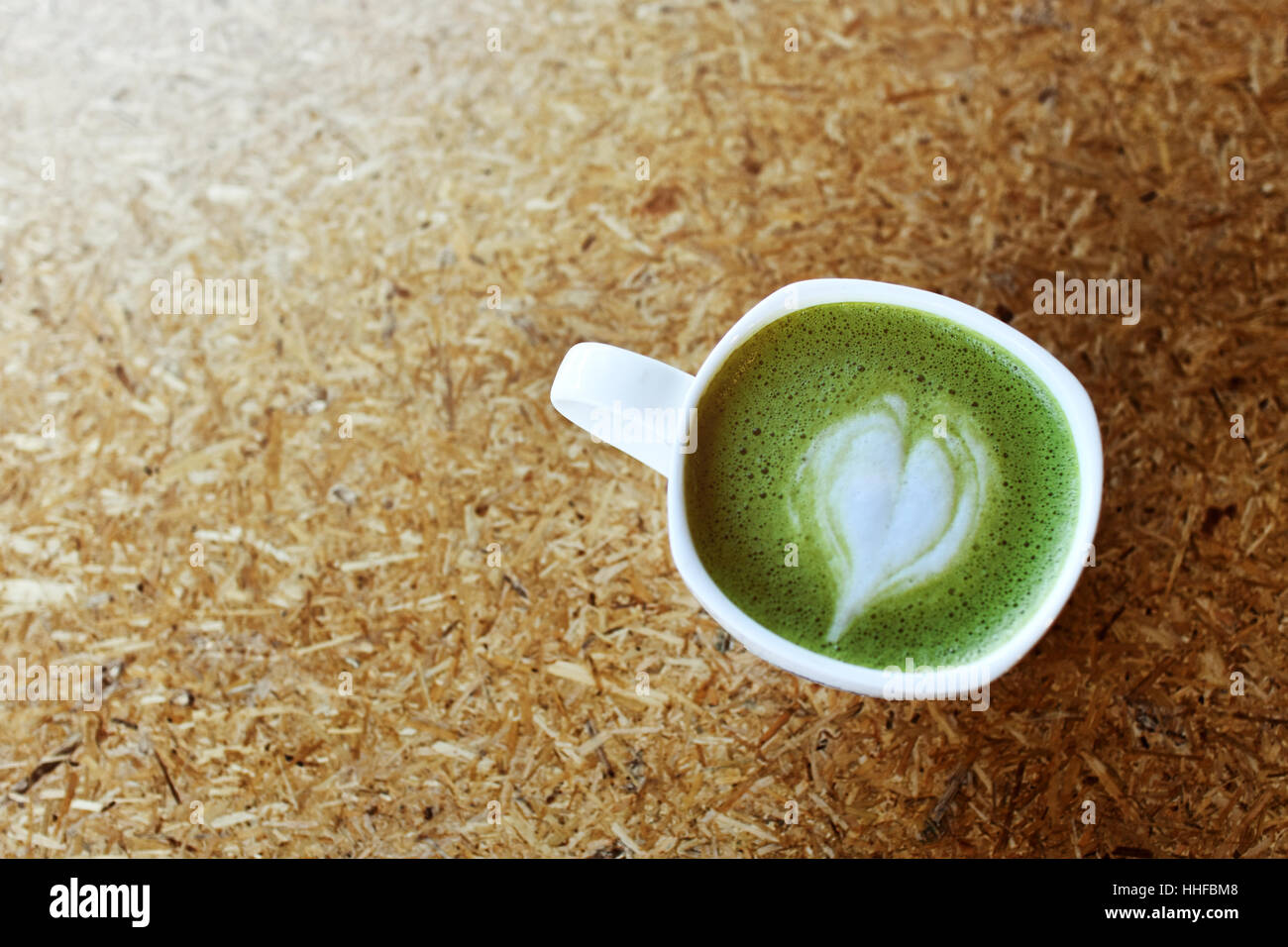 Matcha Green Tea Cup with Heart Latte Art Shape in Top View Perspective and Blank Space of Cork Table for Copy - Stock Image