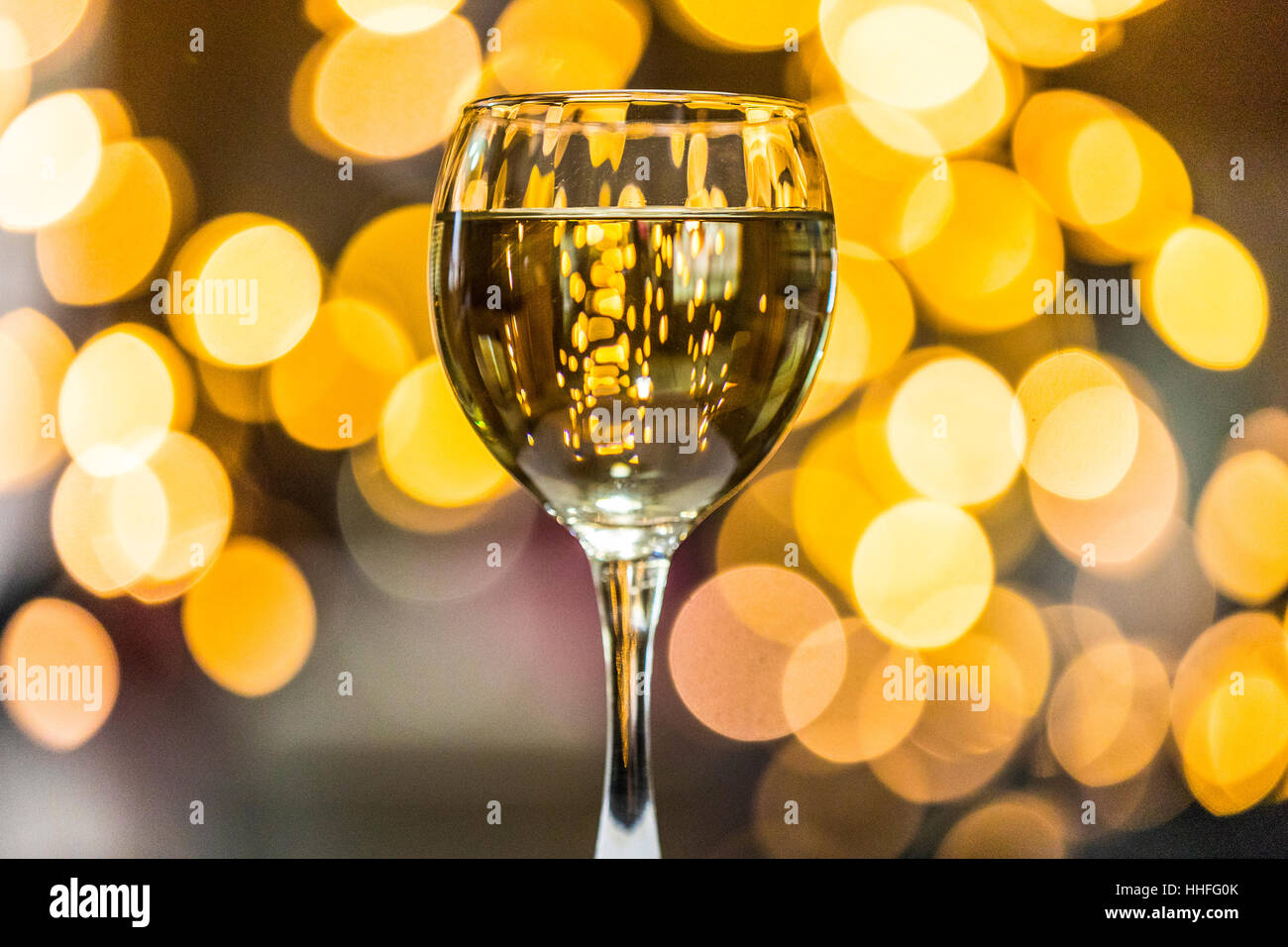 A glass of Pinot Grigio white wine with sparkling lights in the background Stock Photo