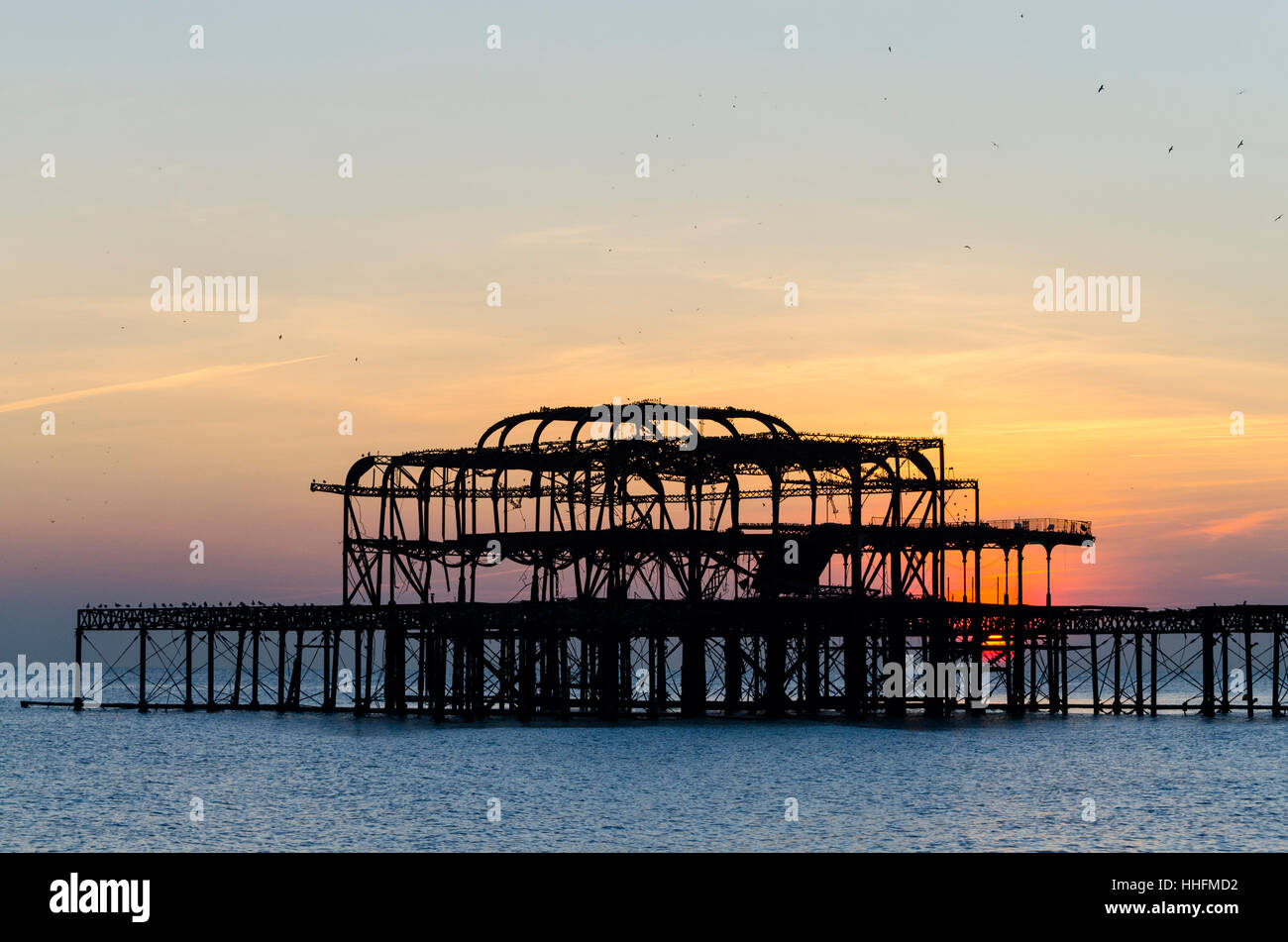 Brighton, UK. 18th January, 2017. A mild sunny winter afternoon brings people to the seafront to watch starling - Stock Image