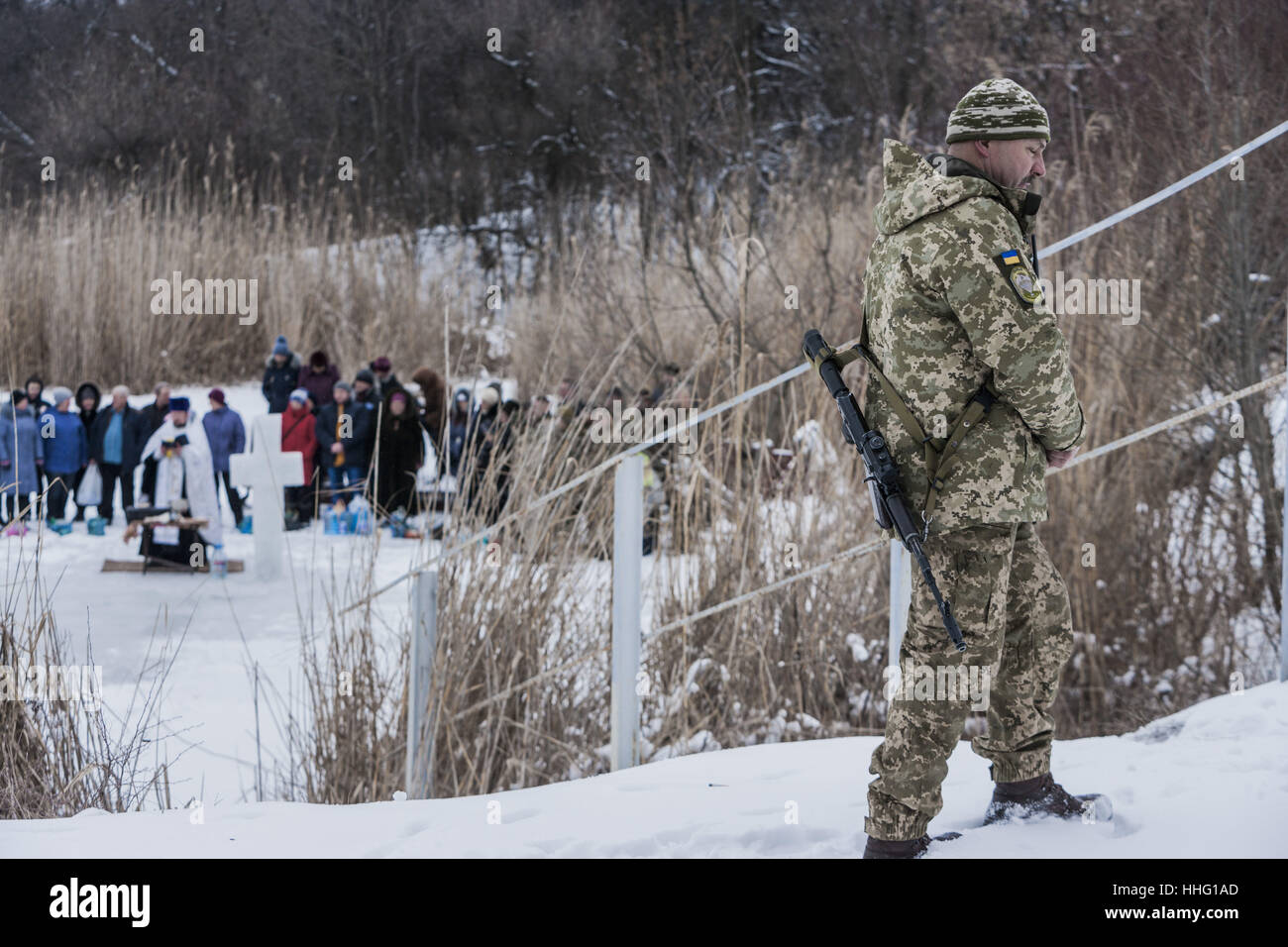 Memryk, Donetsk Oblast, Ukraine. 19th Jan, 2017. Ukrainian soldier watches the events of the orthodox Epiphany in - Stock Image
