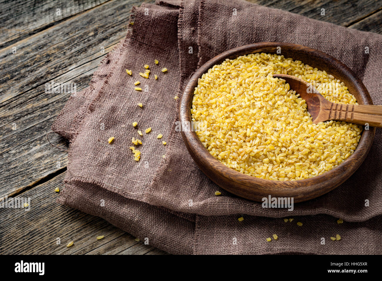 Uncooked bulgur in wooden bowl on wooden table background, rustic style. Bulgur wheat grains - Stock Image