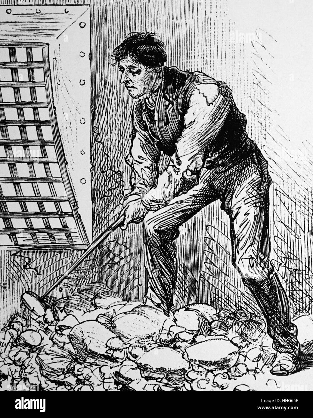 Stone breaking in the casual ward of a typical London workhouse. The stone had to be small enough to pass through - Stock Image