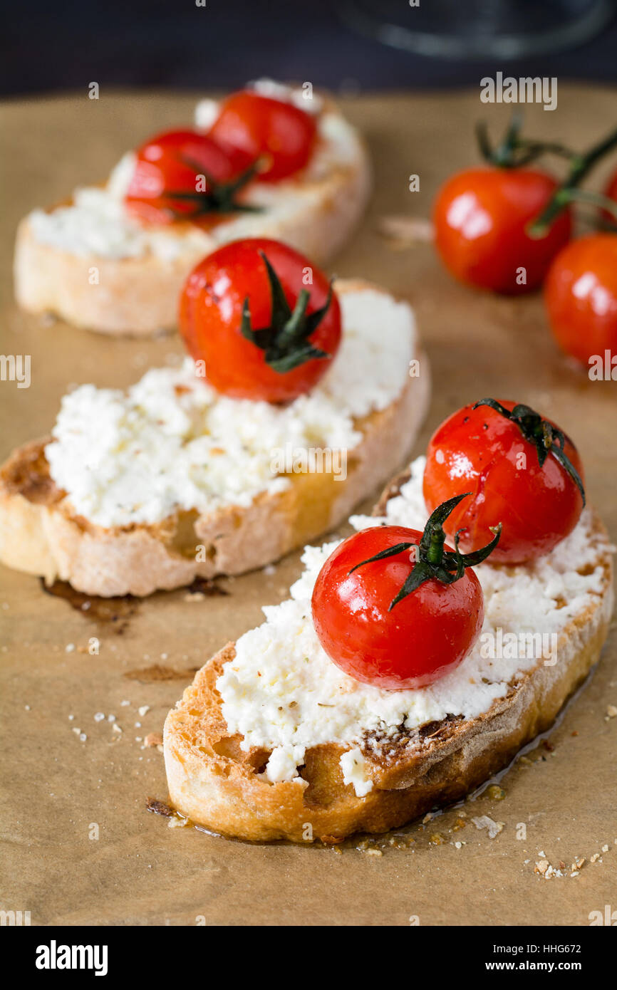 Bruschetta with roasted cherry tomato and fresh ricotta cheese garnished with extra virgin olive oil. Italian cuisine - Stock Image
