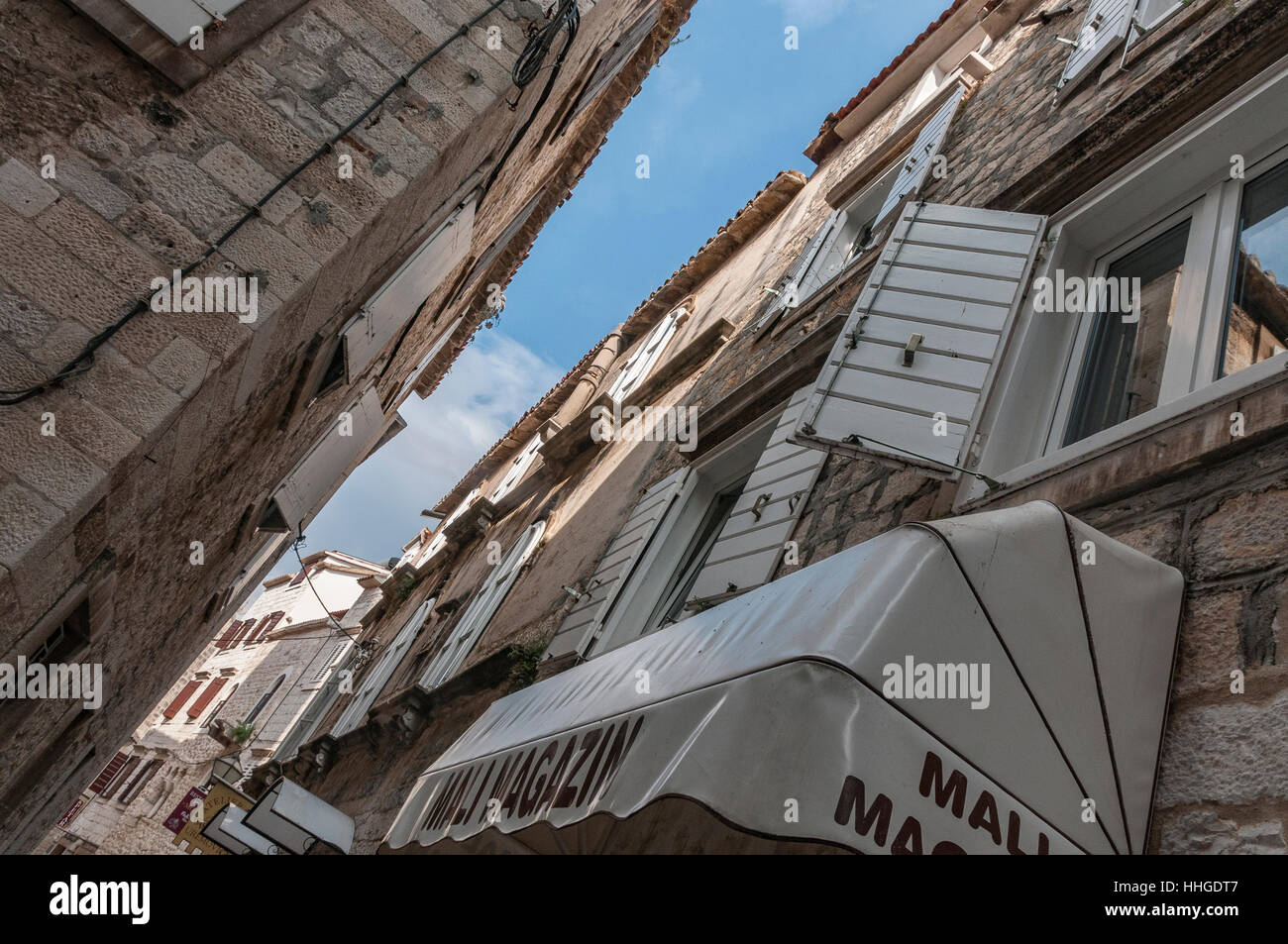 An upward look at some of the gray stone buildings with windows and shutters and an awning in the Old Town of Trogir. - Stock Image