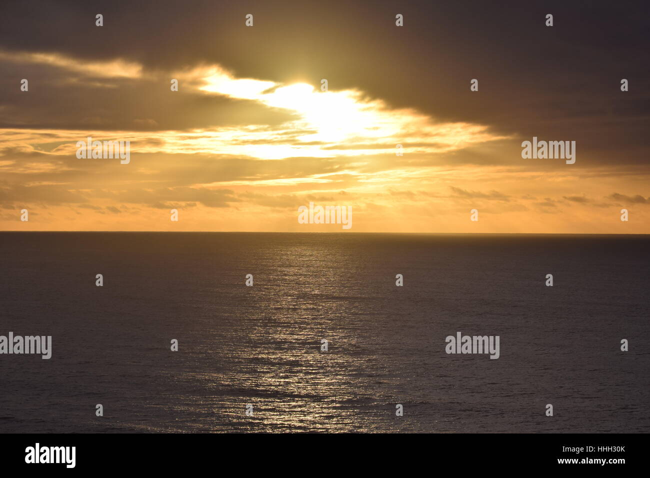 Sunset peeking through the clouds, shimmering light on the Pacific ocean - Stock Image