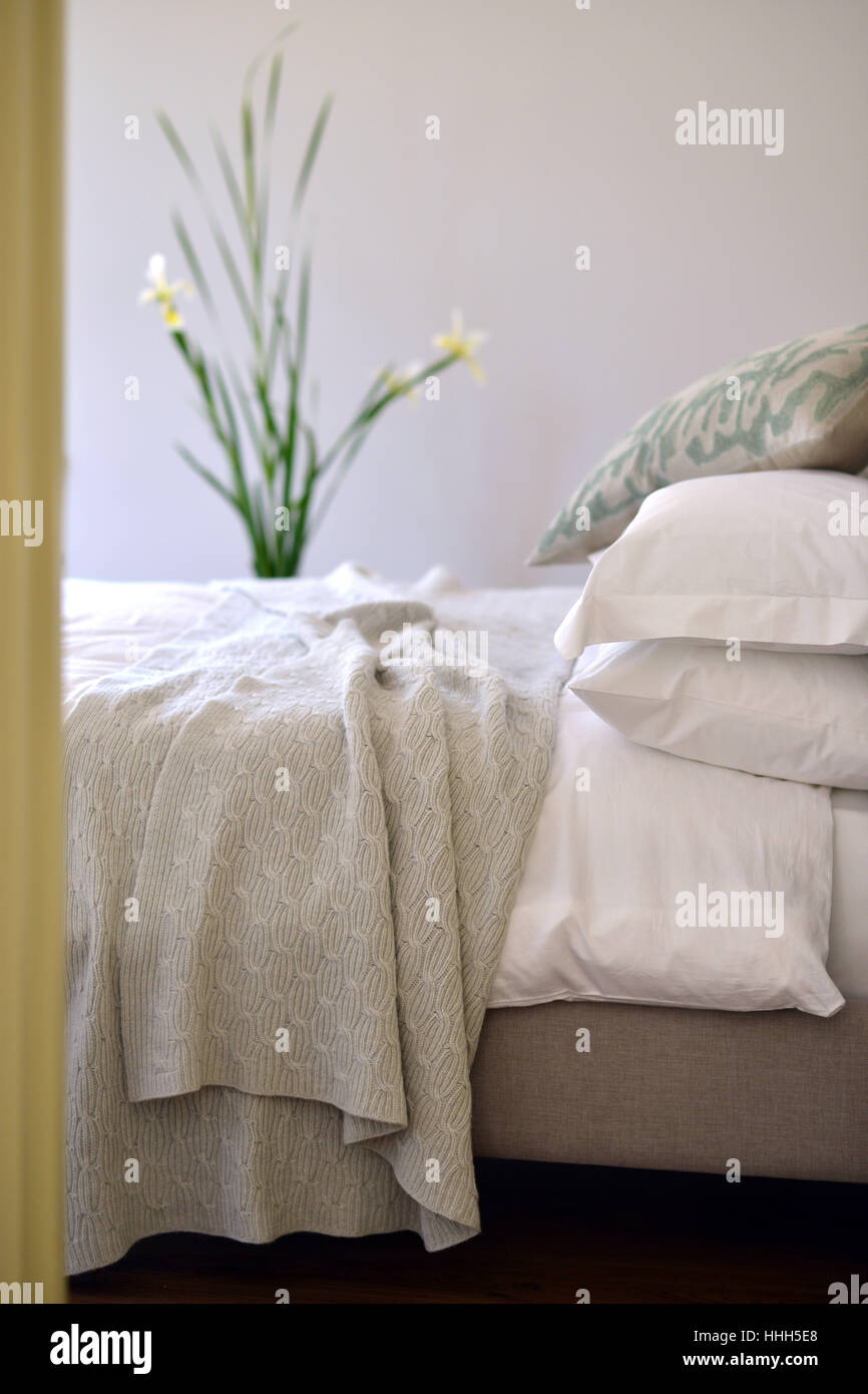 Bed in bedroom setting with luxury bedspread - Stock Image