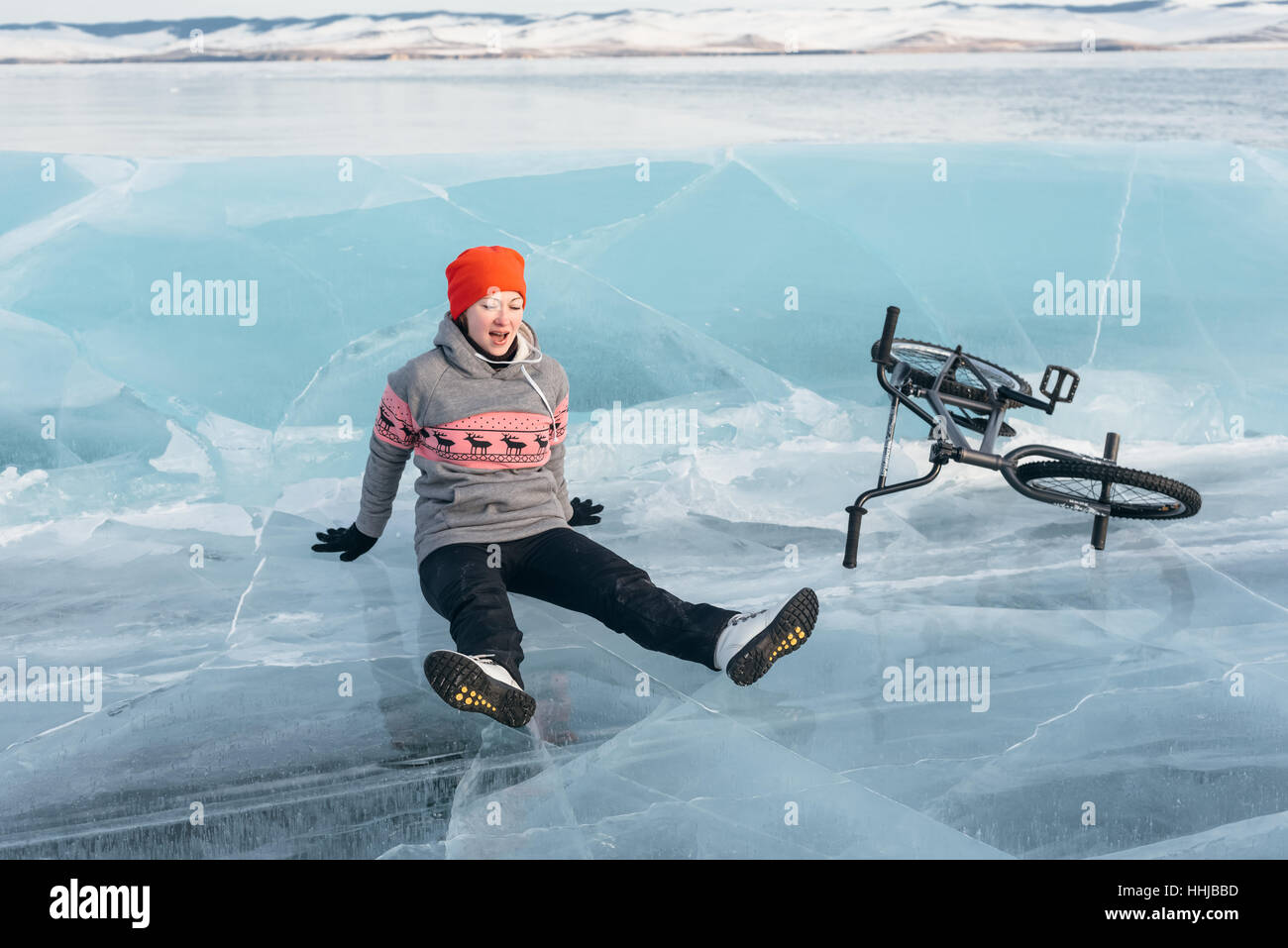 The girl fell from bmx on the beautiful and dangerous ice and rolled down. - Stock Image