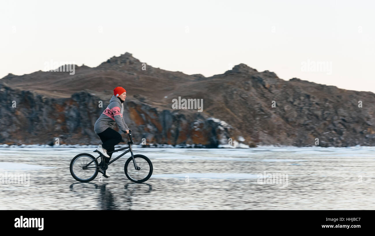 The girl goes on a bmx on the beautiful and dangerous ice. - Stock Image