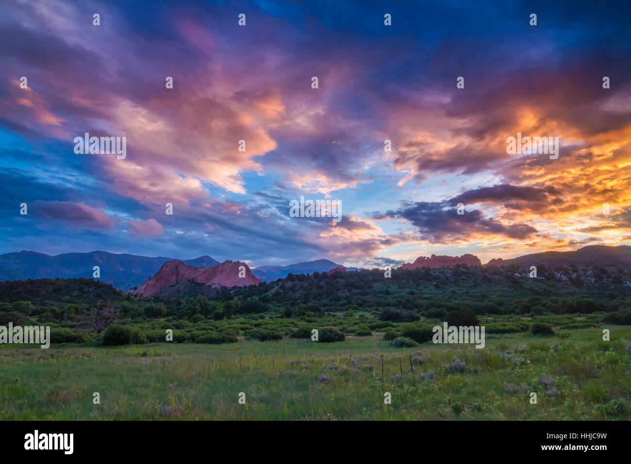 An incredible sunset covers the rocky landscape of Garden of the Gods and Pikes Peak in Colorado Springs, Colorado Stock Photo