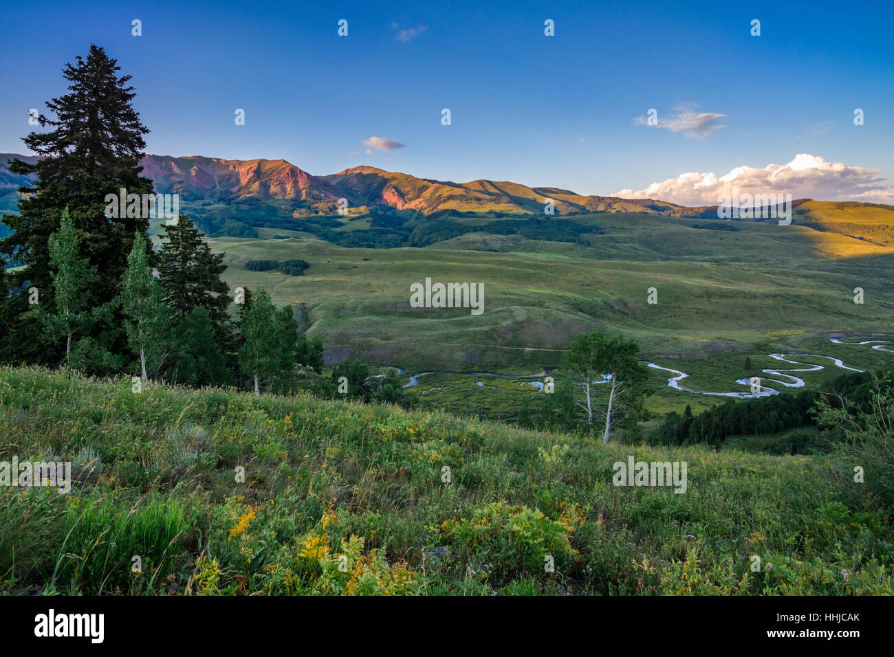 Setting sun makes mountains glow red over green summer fields and a meandering stream near Crested Butte, Colorado - Stock Image