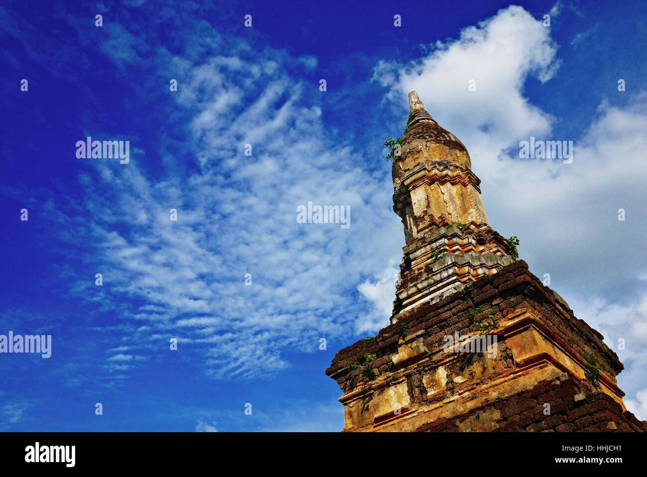 An ancient pagoda against blue sky in Sukhothai historical park, one of the UNESCO cultural World heritage site Stock Photo