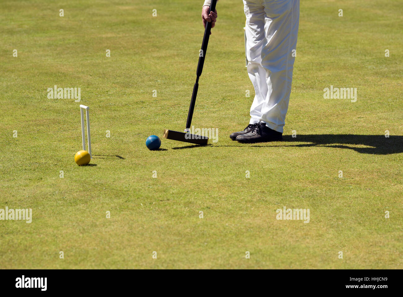 Close-up of a man hitting a croquet ball with a mallet. - Stock Image