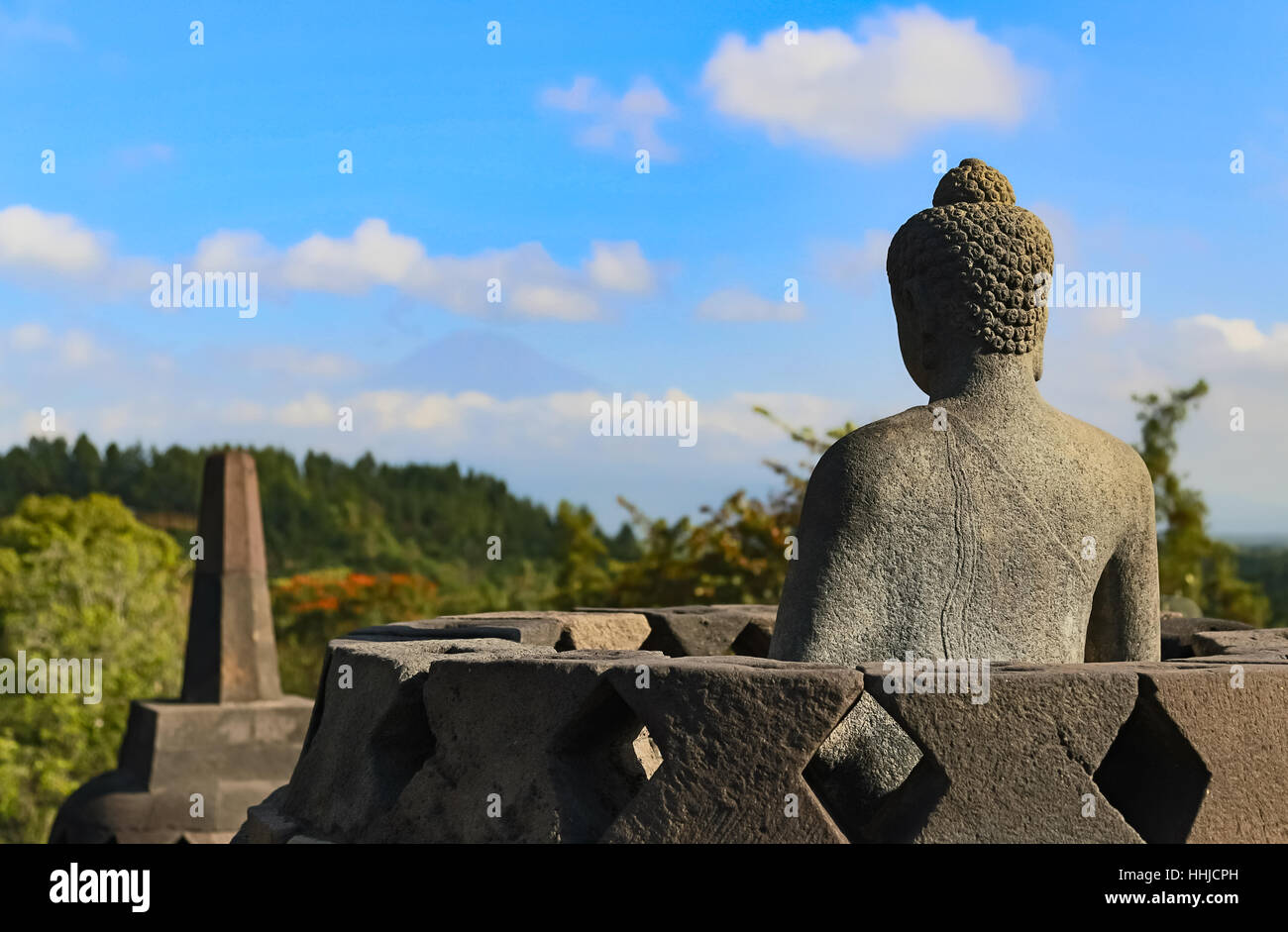 A statue of Buddha looks out towards Mount Merapi from the Borobudur Temple in Magelang, Central Java, Indonesia. - Stock Image