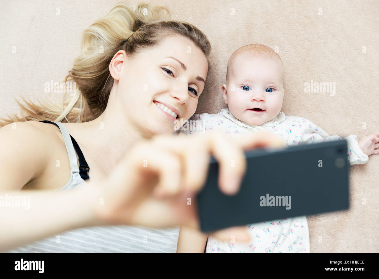 mother and little infant baby taking selfie with phone in bed - Stock Image