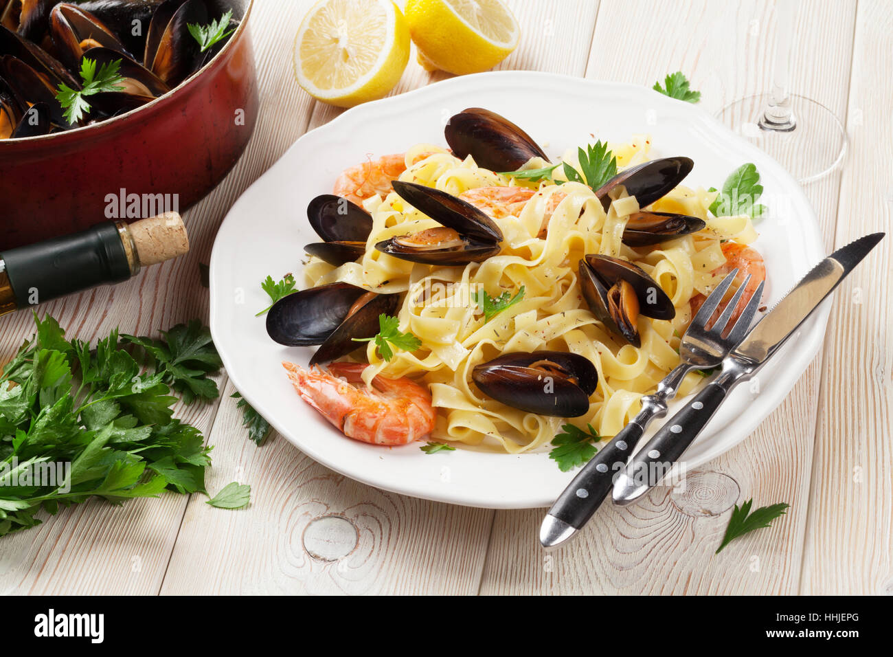 Pasta with seafood and white wine on wooden table. Mussels and prawns Stock Photo