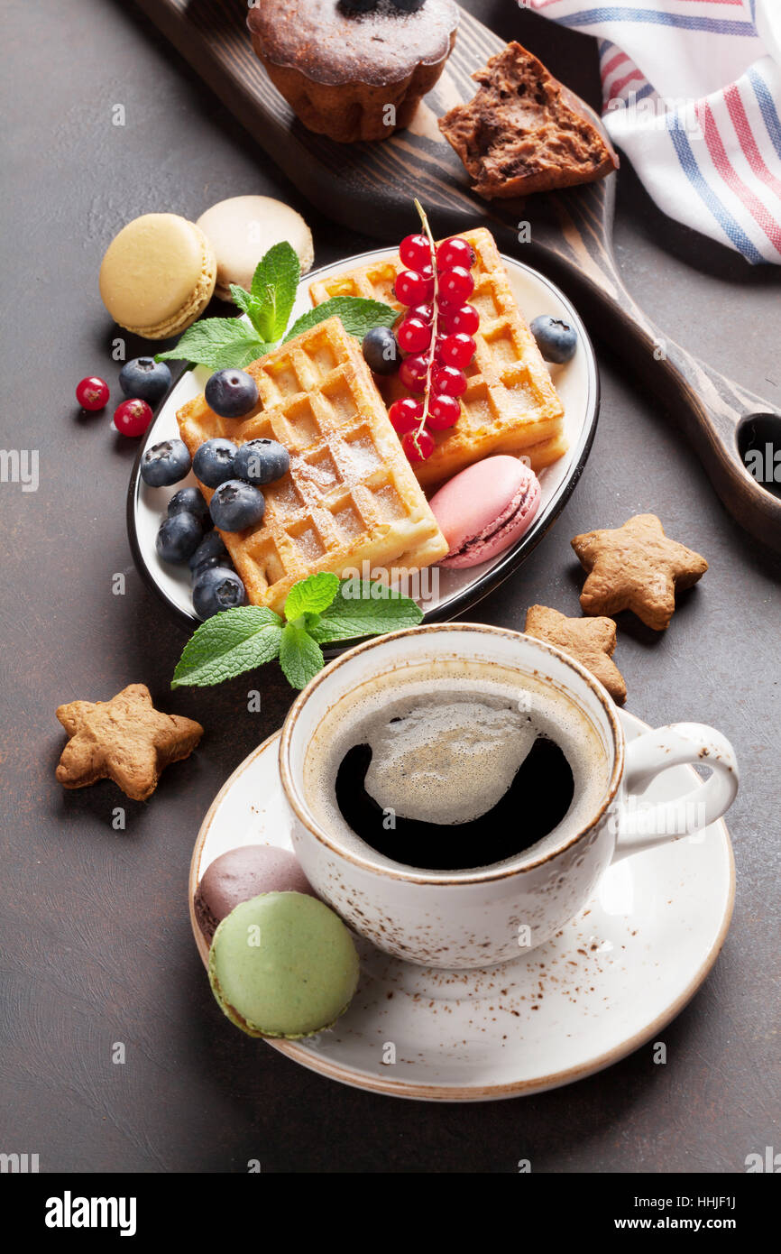 Coffee, sweets and waffles with berries - Stock Image