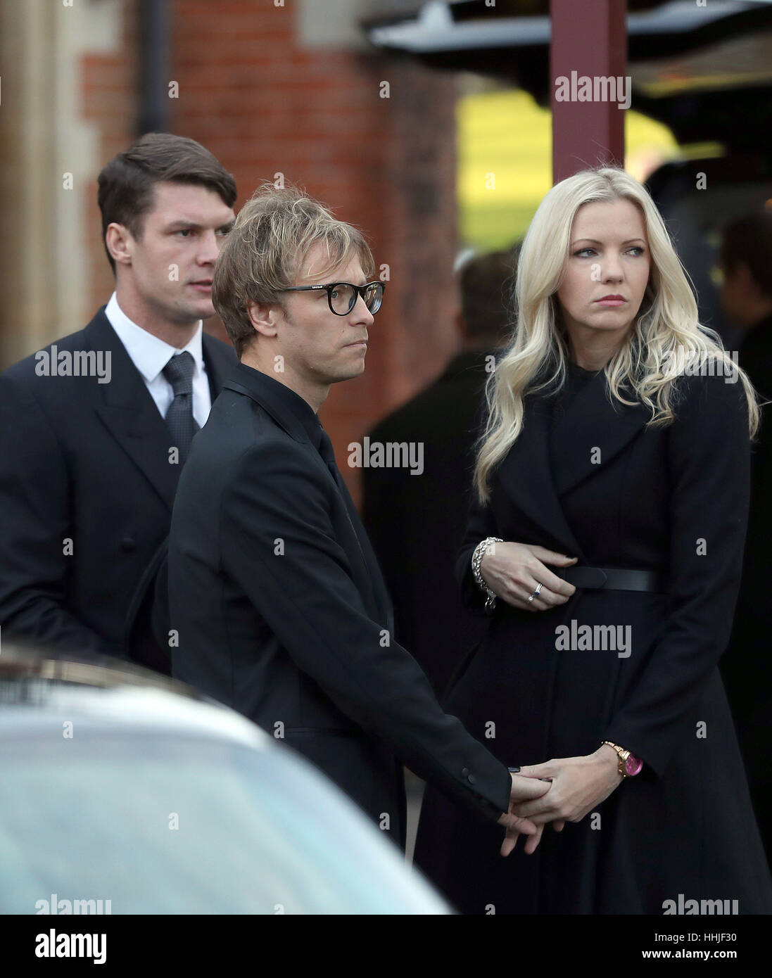 Rachel Gretton and Rick Parfitt Jnr (centre) arrive at Woking Crematorium for the funeral of his father and Status - Stock Image