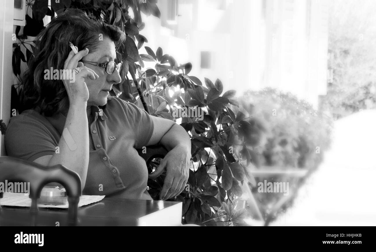 Adult woman smoking sitting in her home. - Stock Image